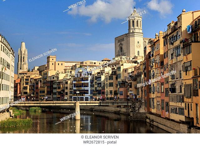 Cathedral towers above distinctive historic colourful arcaded houses and Onyar River, Girona, Girona Province, Catalonia, Spain, Europe