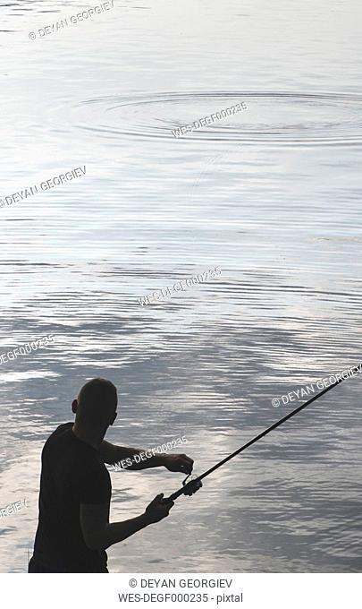 Silhouette of man fishing at dam