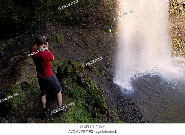 A young couple has some fun behind Moll Falls, Wells Gray Park, Clearwater, British Columbia, Canada