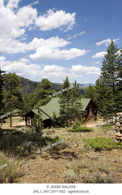 EXTERIORS: Dark brown cabin used as summer home in colorado, stone foundation, pine trees