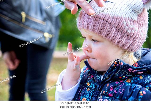 Female toddler with finger in her mouth in park