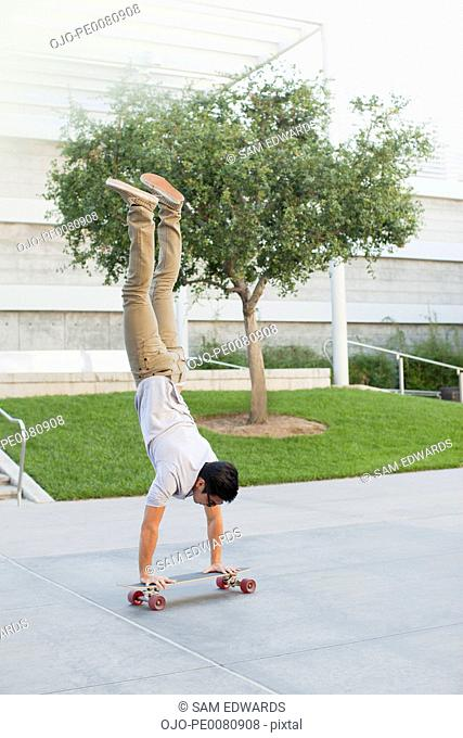 Man doing handstand on skateboard