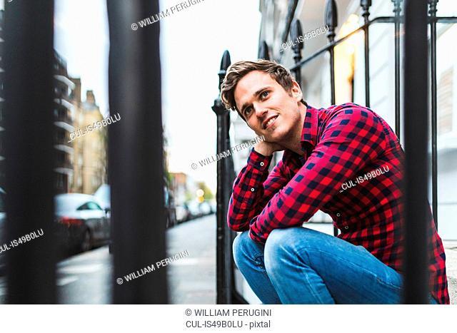 Portrait of mid adult man, sitting beside railings, smiling