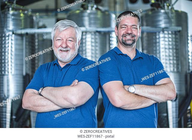 Master distiller standing in distillery with arms crossed