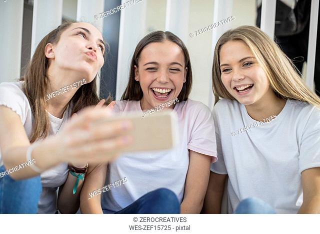 Happy teenage girls sharing cell phone in school