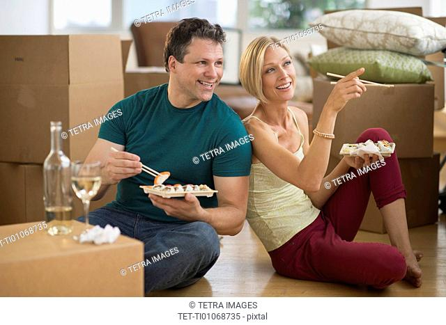Couple eating sushi in new home