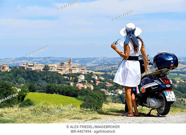 Woman with white sunhat next to Vespa Primavera scooter, Corinaldo, Marche, Italy