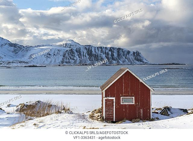 Red cabin in the snow on Ramberg beach, with mountains in the background. Flakstad municipality, Nordland county, Northern Norway, Norway