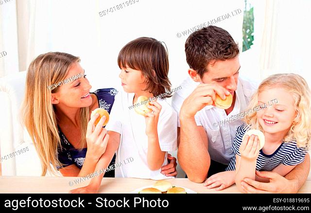 Lively family eating burgers in the living room