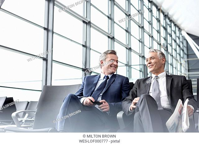 Two smiling businessmen at airport departure lounge