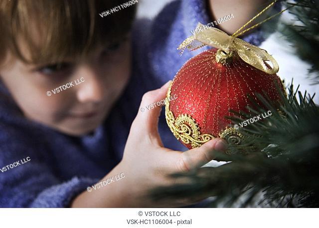 Girl putting ornament on Christmas tree
