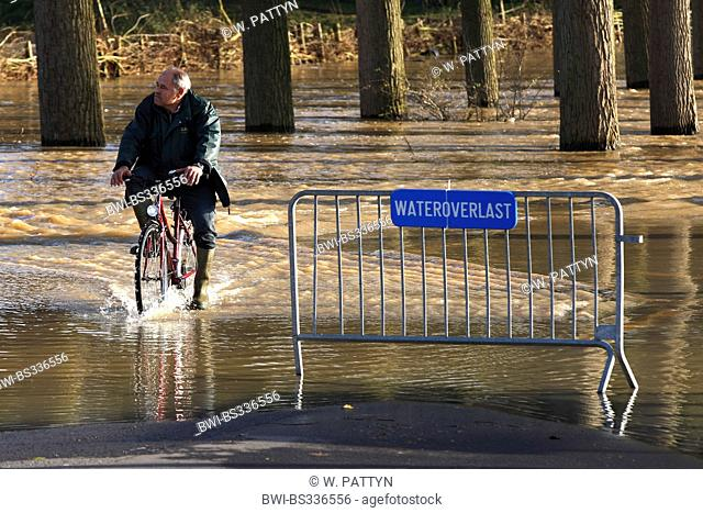 cyclists on flooded road, Belgium, Durme