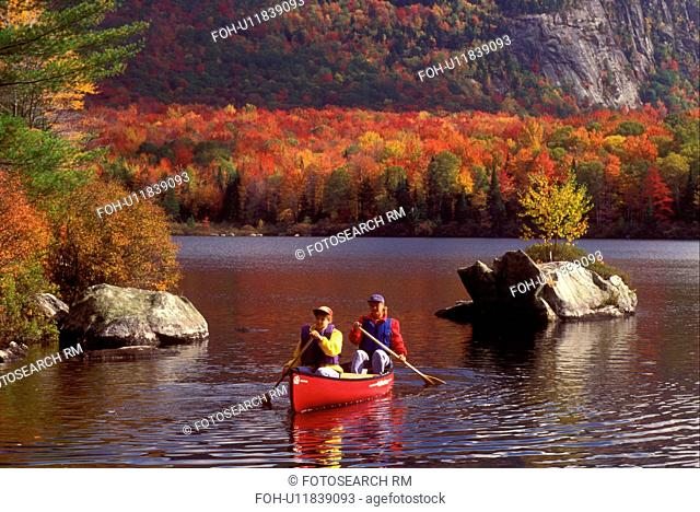 Vermont, canoe, canoeing, Mother and daughter paddling a red canoe on a fall day on Marshfield Pond in Marshfield. Mad River Canoe Products