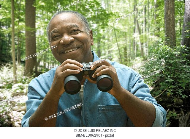 African man holding binoculars in forest