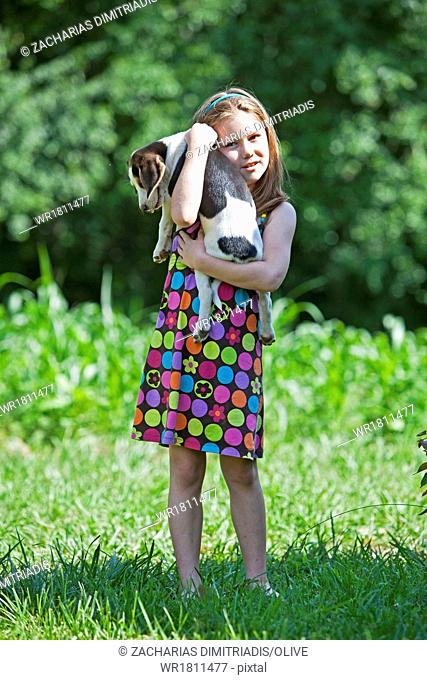 Young girl holding hunting dog puppy