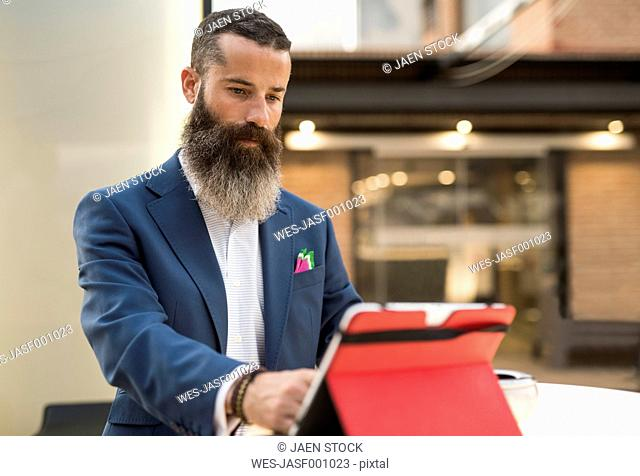Bearded man looking tablet at terrace