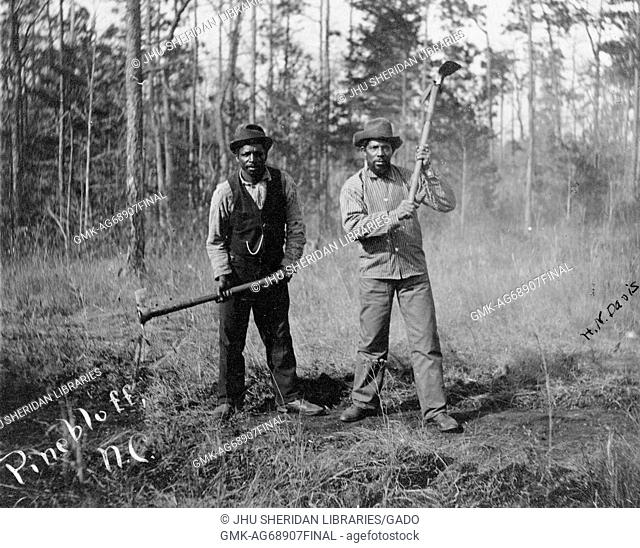 Full length standing portrait of two African American workers with neutral expressions, wearing hats, pants, shoes, button-up shirts and one wearing a suit vest