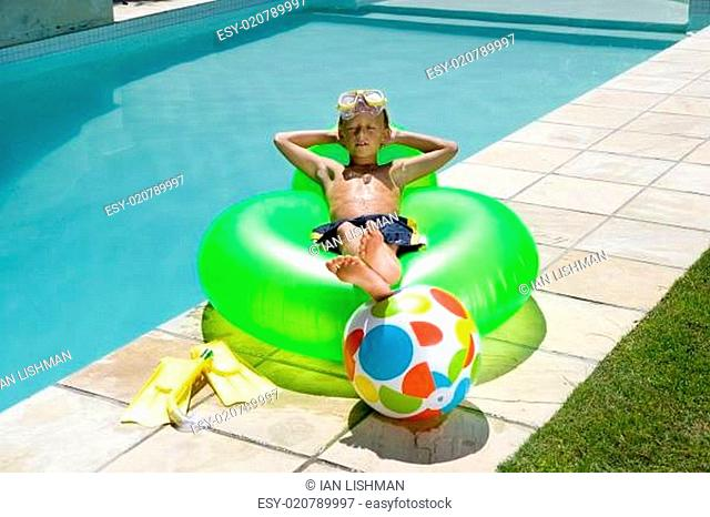 Boy (9-11) on inflatable chair by swimming pool, arms behind head