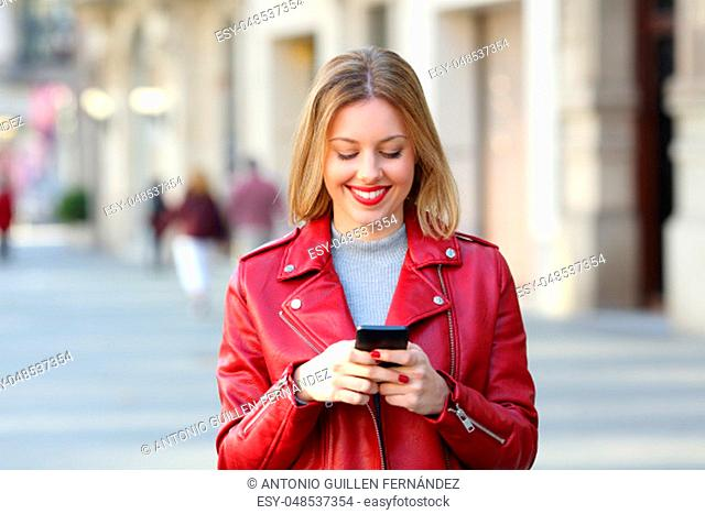 Front view portrait of a fashion blonde walking on the street and using a smart phone