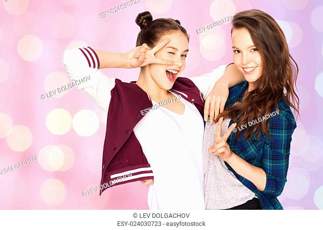 people, friends, teens and friendship concept - happy smiling pretty teenage girls showing peace hand sign over pink holidays lights background
