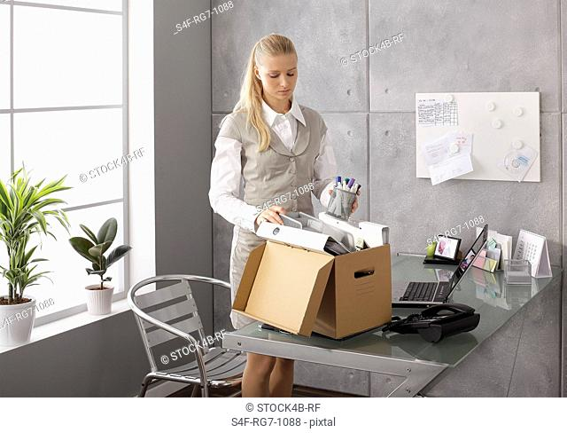 Businesswoman packing up office belongings