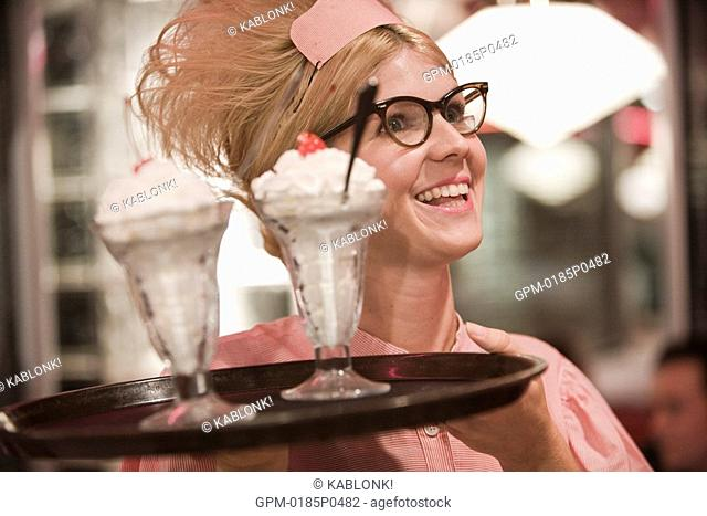 Close-up of young waitress in 1950s style uniform carrying tray of ice cream sundaes