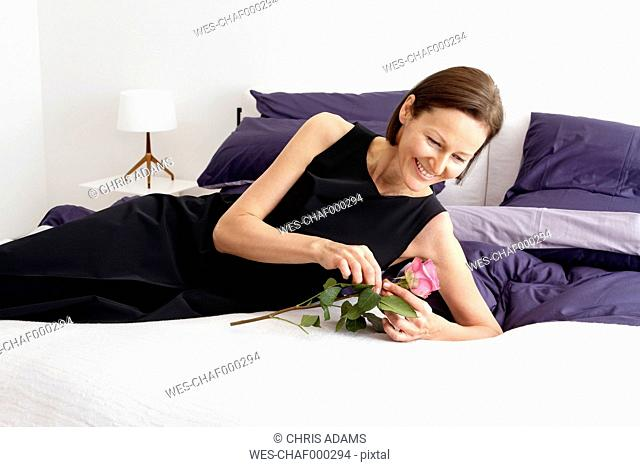 Smiling mature woman lying on bed with a rose