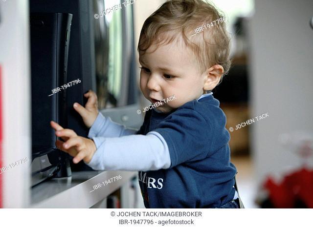 Little boy, 1 year, exploring a DVD player