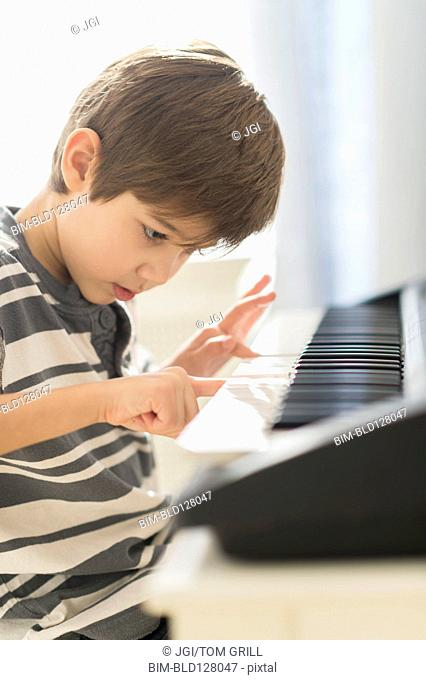 Hispanic boy practicing piano