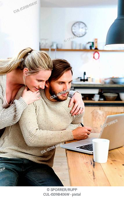 Mid adult couple looking at laptop in kitchen