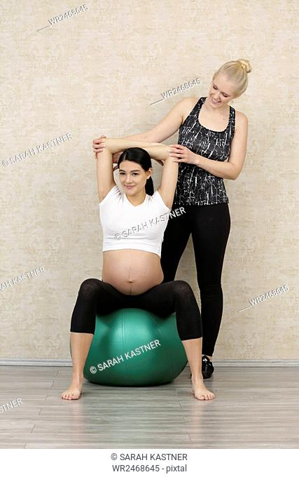 Pregnant woman doing fitness exercise with a personal trainer