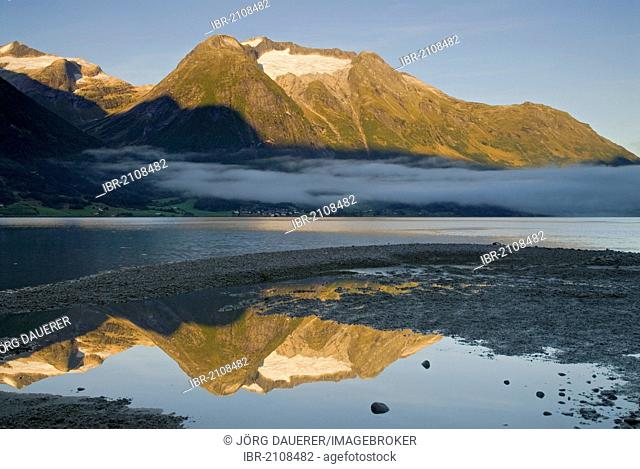 Morning fog over Strynevatnet, surrounded by mountains, reflected in a small puddle, as seen from Hjelle, Loen, Sogn og Fjordane, Norway, Europe