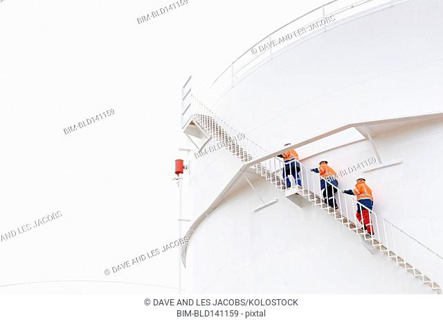 Caucasian technicians climbing fuel storage tank staircase