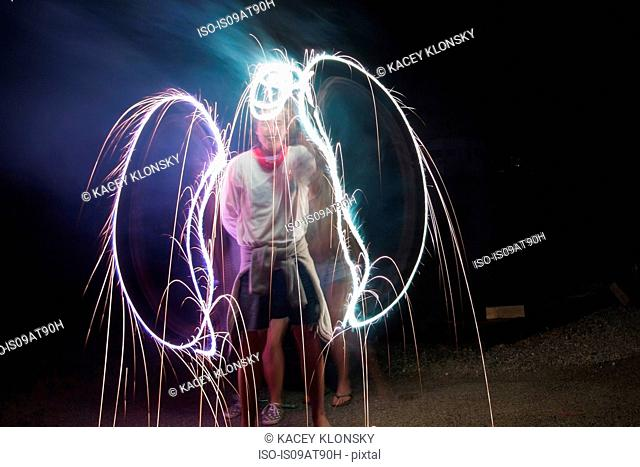 Two adult friends making sparkler angel wings in darkness on Independence Day, USA