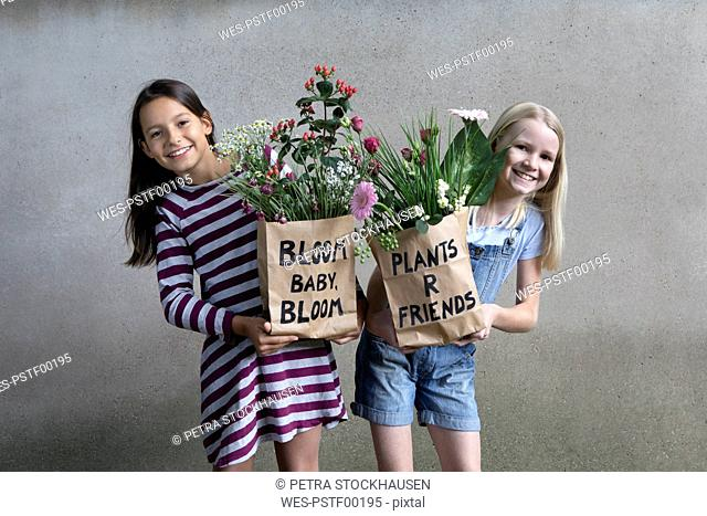 Portrait of two smiling girls holding paper bags with flowers