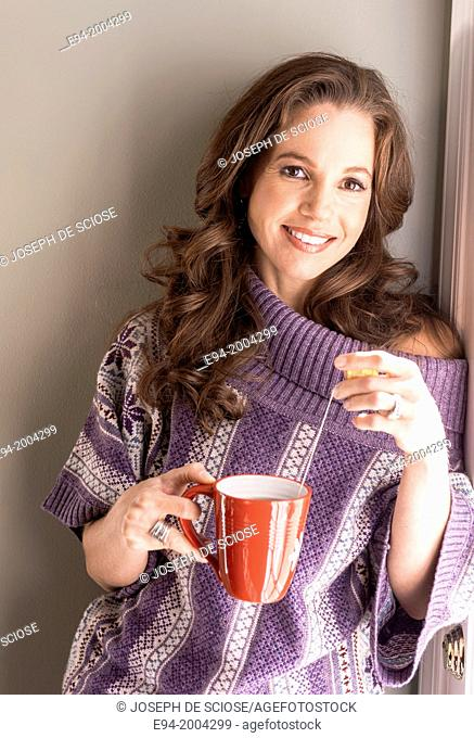 37 year old brunette woman wearing a big sweater and holding a cup of steaming tea in a kitchen setting