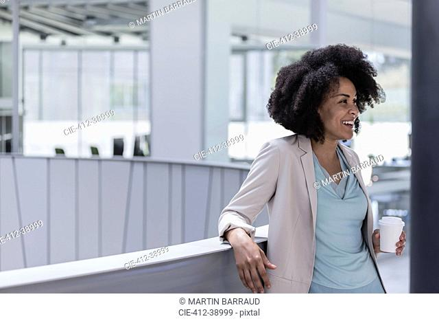 Smiling businesswoman drinking coffee at office railing