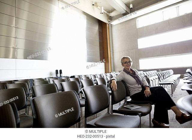 Portrait confident woman sitting in empty auditorium