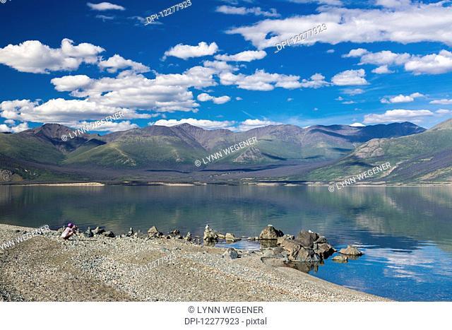 Woman photographs stacked rocks along Kluane Lake, Yukon Territory, Canada