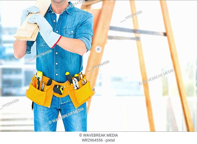 Carpenter wearing a tool belt and coverall is holding a wooden board against ladder background