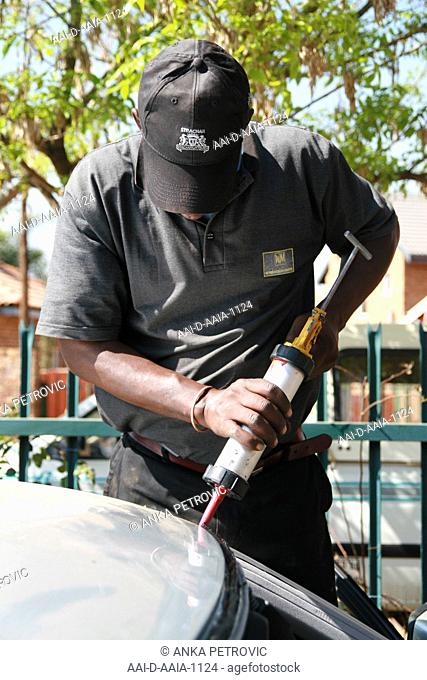 Man fixing the windscreen of a car, South Africa