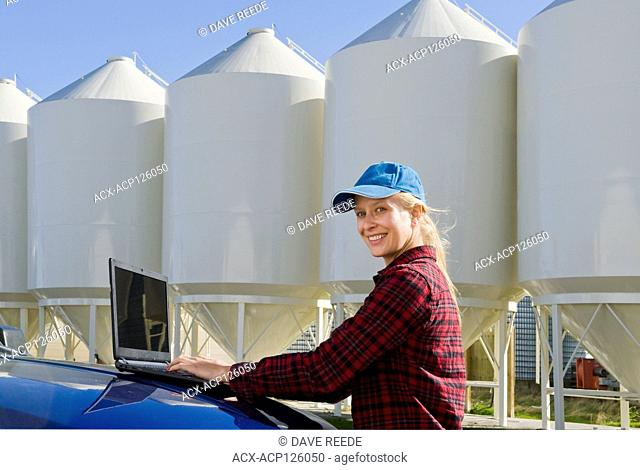 girl using a computer next to seed storage hopper bins in a farmyard, near Dugald, Manitoba