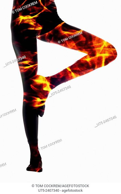 Woman's legs superimposed with fire in studio setting