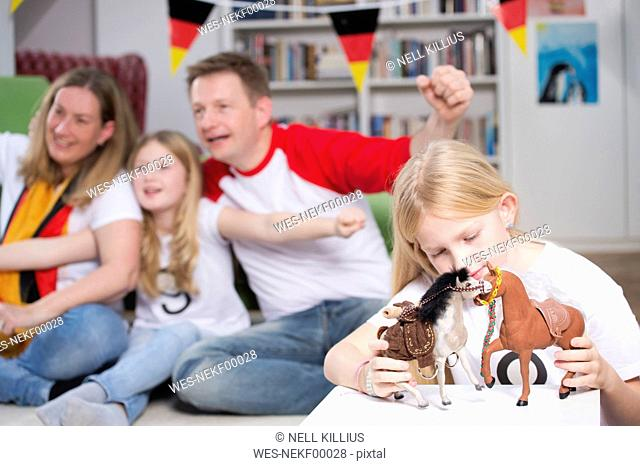 Family watching football world cup on TV, while little girl is playing with toys