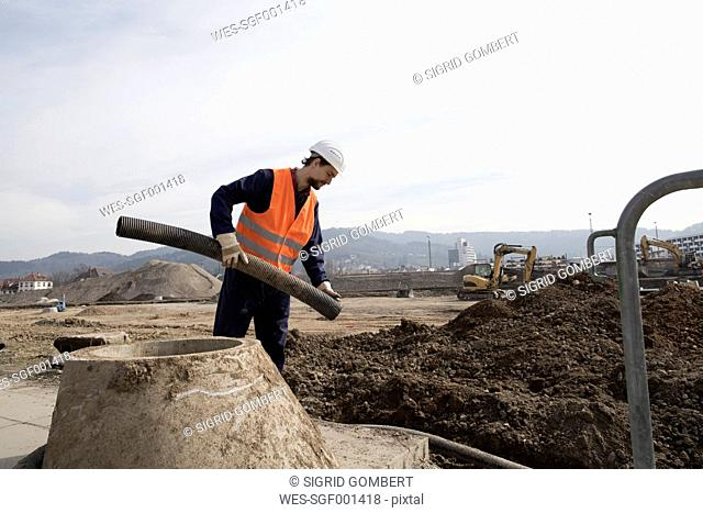 Builder holding pipe on construction site