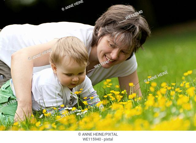 mom andtoddler son crawling through grass
