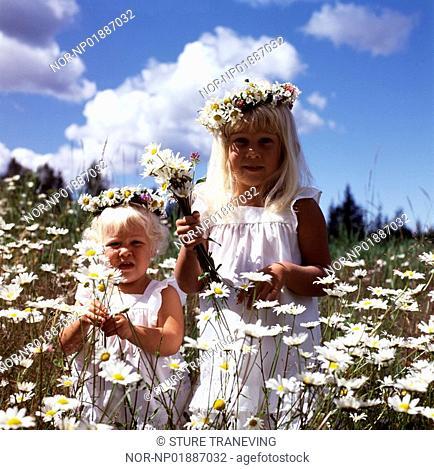 Two girls in a flower meadow wearing wreaths in midsummer time