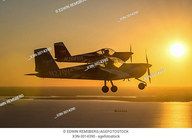 Two Vans RV-12 light sport aircrafts fly in formation together with the dramatic setting sun behind them on the Chesapeake Bay, Stevensville, Maryland, USA