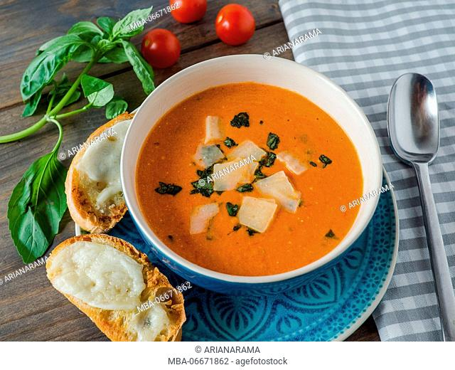 Fresh tomato soup with baked cheese Ciabatta on a wooden table, top view