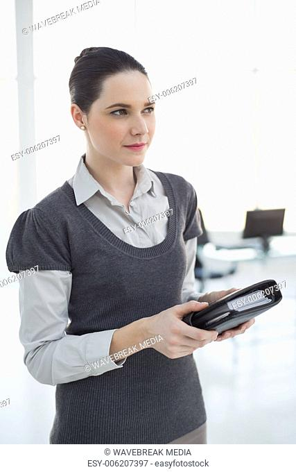 Pensive young businesswoman holding datebook